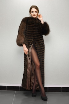 Portrait of attractive lady with long legs in fur coat posing near wall. natural makeup.