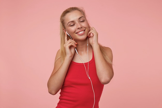 Ritratto di attraente giovane femmina dai capelli lunghi in posa con gli occhi chiusi, deliziando la musica nei suoi auricolari, indossa la camicia rossa