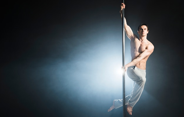 Portrait of attractive male model performing a pole dance