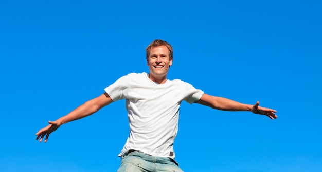Portrait of an attractive man jumping in the air outdoor