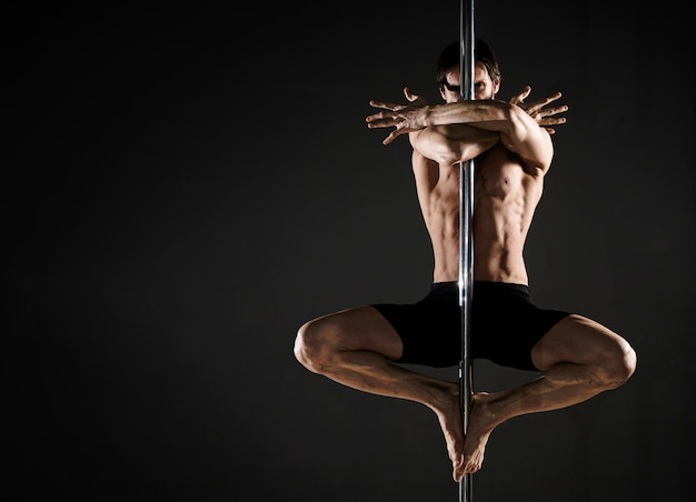 Portrait of attractive man performing a pole dance