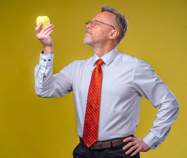 Portrait of attractive man posing on camera. holding yellow apple in hand. isolated over white background.