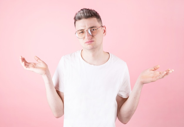 Portrait of attractive man showing i don't know gesture isolated over pink background