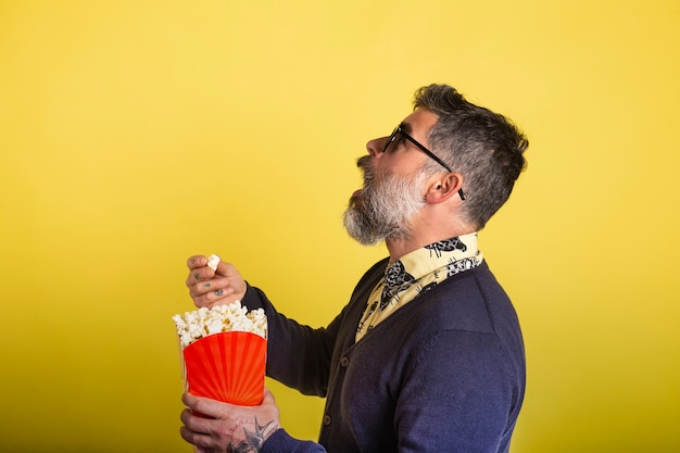 Portrait of attractive man with beard and sunglasses eating popcorn from profile to camera on yellow background.