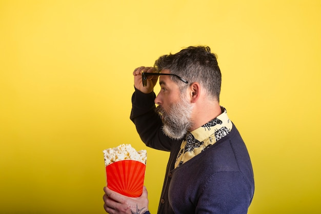 Portrait of attractive man with beard and sunglasses holding a box of popcorn in profile in amazed camera looking up at the glasses on yellow background.