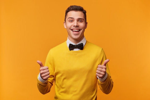 Portrait of attractive man with thumbs up looks like has a success, smartly dressed in yellow sweater over white shirt with bow-tie