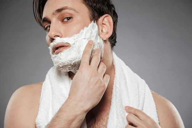 Portrait of attractive man with towel on neck putting shaving foam on face, while having morning skincare isolated over gray wall