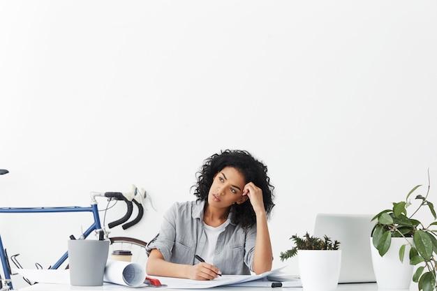 Ritratto di attraente architetto donna di razza mista con capelli ricci neri sdraiato sulla sua scrivania