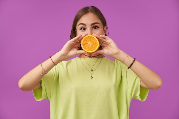 Portrait of attractive, nice looking girl holding orange over her mouth with two hands. standing over purple wall. wearing green t-shirt, bracelets, rings and necklace