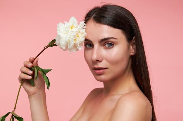 Ritratto di attraente, bella ragazza con lunghi capelli castani e pelle sana, toccando la testa con un fiore. guardando, primo piano, isolato sopra il muro rosa pastello