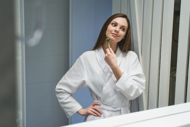Portrait of an attractive pleased calm caucasian female looking at herself in the bathroom mirror