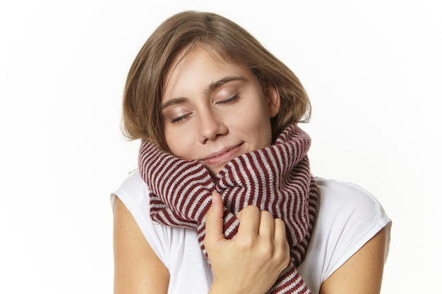 Portrait of attractive pleased young european female with natural make up closing her eyes and smiling joyfully, enjoying soft woolen scarf, warming up on cold winter day