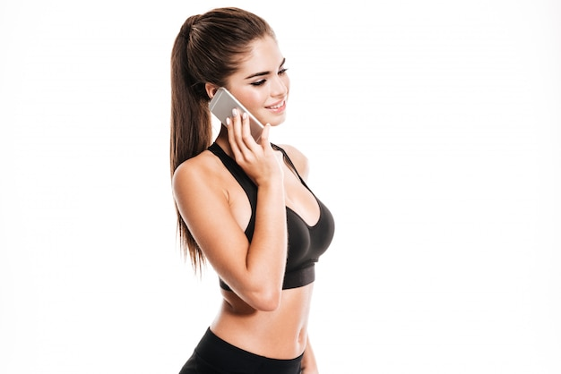 Portrait of attractive positive fitness girl talking on mobile phone