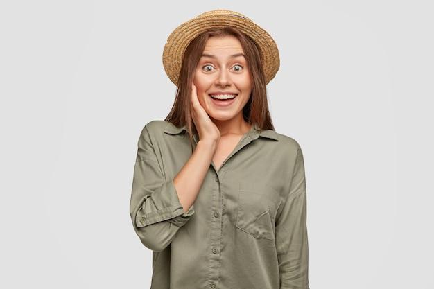 Ritratto di attraente giovane donna positiva stupita da notizie sbalorditive