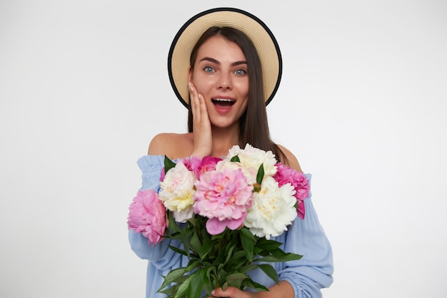 Portrait of attractive, pretty girl with long brunette hair. wearing a hat and blue dress. holding bouquet of flowers and touching her cheek. watching  isolated over white wall