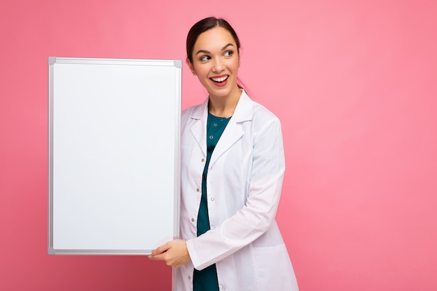 Portrait of attractive pretty young positive brunette woman wearing medical white coat holding white magnetic board for mock up isolated over pink background with copy space.