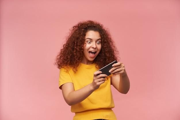 Ritratto di una ragazza attraente e rossa con i capelli ricci che indossa la maglietta gialla
