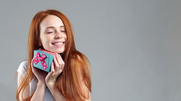 Portrait of an attractive redhead young woman standing in isolation, holding a gift box