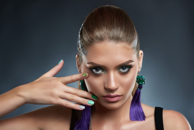 Portrait of attractive and seductive woman with shiny manicure and makeup in green colors. beautiful brunette with long violet earring, touching face. beauty concept.