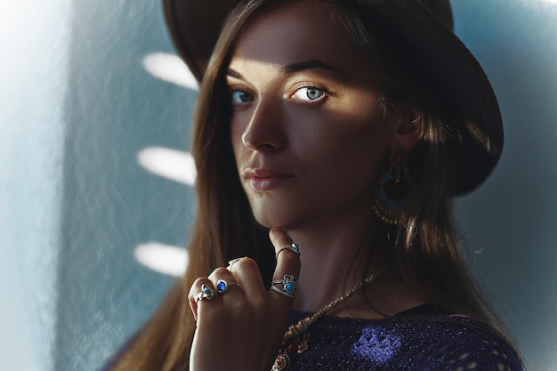 Portrait of attractive serious stylish brunette woman in a hat wearing jewelry with overlays shadow on eyes