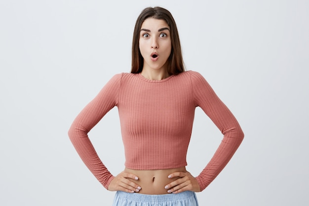 Portrait of attractive sexy dark-haired student girl with long hairstyle in pink top and blue shorts looking  with surprised expression, holding hands on waist being excited