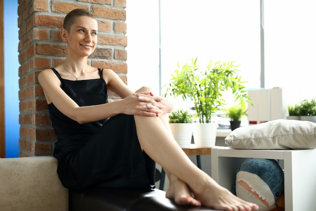 Portrait of attractive short haired female sitting on couch and posing for picture. smiling young woman in simple black dress in living room. modeling and beauty concept
