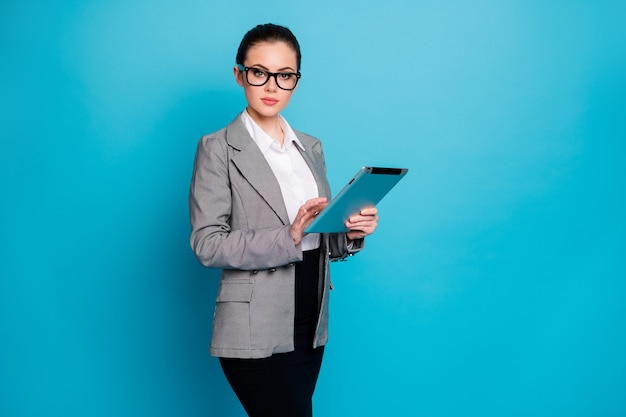 Portrait of attractive skilled lady specialist researching data market using device isolated on bright blue color background