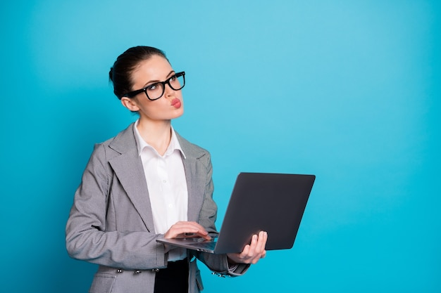 Portrait of attractive smart skilled minded lady it specialist holding in hands laptop creating idea isolated over bright blue color background