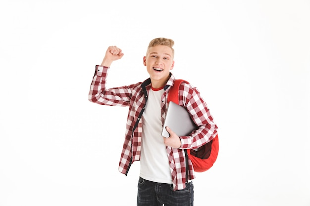 Portrait of attractive smart teenage boy wearing plaid shirt and braces posing with silver notebook and backpack while gesturing in joy, isolated over white wall