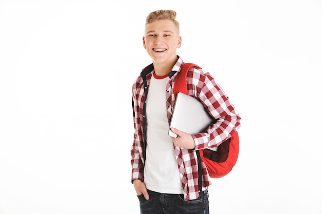 Portrait of attractive smart teenage boy wearing plaid shirt and braces smiling and looking on camera while holding silver laptop, isolated over white wall