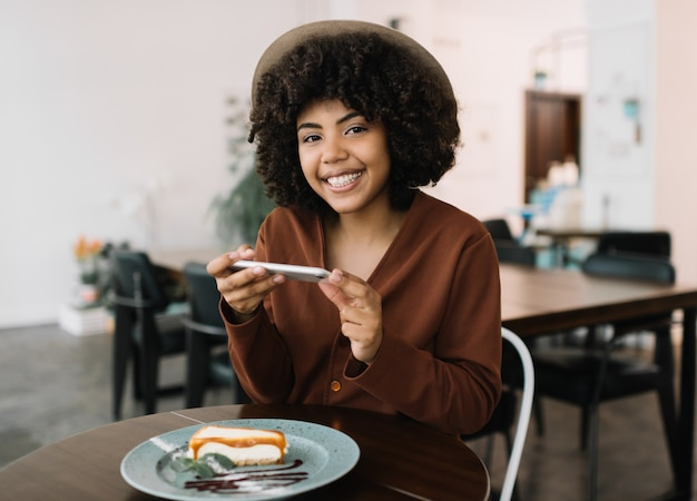 Portrait of attractive smiling african american woman using smartphone and taking mobile photography cheesecake on plate. positive successful food blogger making posts in social networks