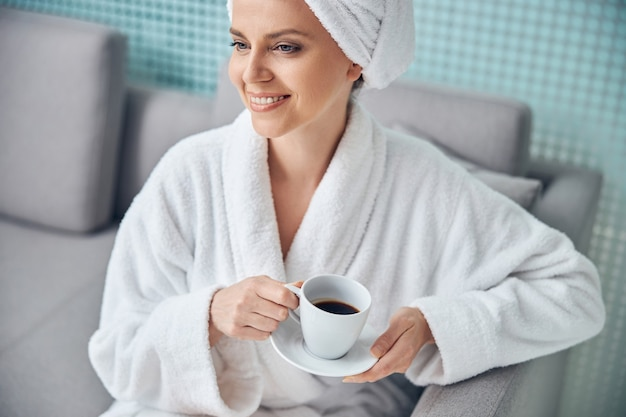 Portrait of an attractive smiling dreamy female with a towel on her head looking away