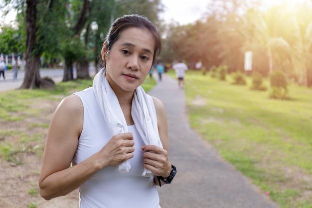 屋外でのトレーニングスポーツエクササイズの後に休んでいる白いタオルで肖像画の魅力的な笑顔フィット女性
