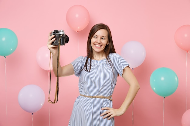 Portrait of attractive smiling happy woman in blue dress do selfie on retro vintage photo camera on pastel pink background with colorful air balloons. birthday holiday party, people sincere emotions.