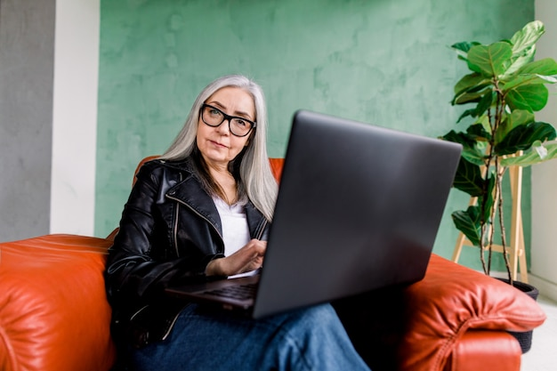 Portrait of attractive smiling senior woman wearing eyeglasses and black leather jacket, posing to camera while sitting in comfortable red armchair and using her laptop computer