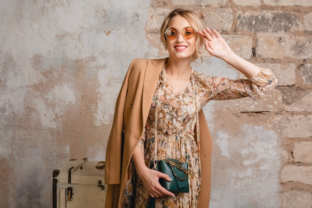 Portrait of attractive smiling stylish blonde woman in beige coat walking in street against vintage wall