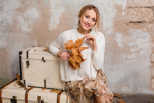 Ritratto di donna bionda elegante sorridente attraente in maglione lavorato a maglia bianco che si siede sulle valigie in strada contro il muro d'epoca