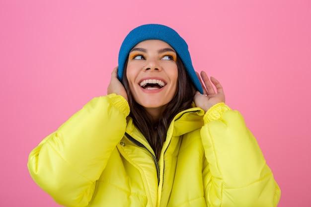 Ritratto di donna alla moda sorridente attraente che posa sulla parete rosa in piumino invernale colorato di colore giallo, indossa un cappello lavorato a maglia blu, vestito con abiti caldi, tendenza della moda