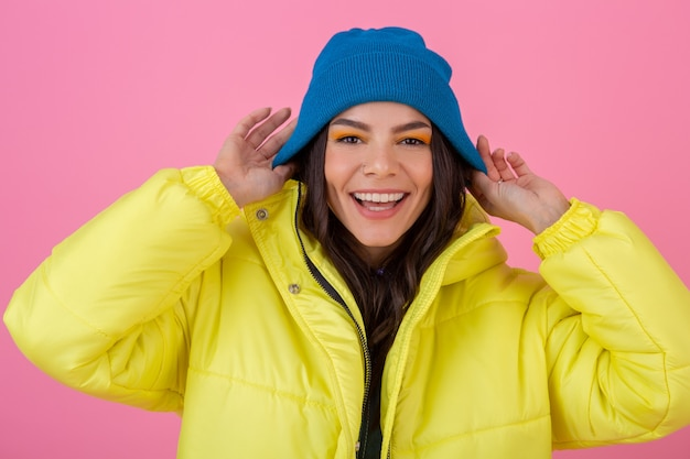 Portrait of attractive smiling stylish woman posing on pink wall in colorful winter down jacket of yellow color, wearing blue knitted hat, dressed in warm clothes, fashion trend