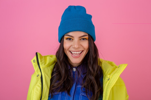 Portrait of attractive smiling stylish woman posing in winter fashion look on pink wall in bright neon yellow jacket, wearing blue knitted hat, dressed in warm clothes