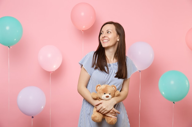 Portrait of attractive smiling woman in blue dress looking aside holding and hugging teddy bear plush toy on pink background with colorful air balloons. birthday holiday party people sincere emotions.