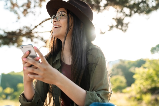 Portrait of attractive smiling woman wearing stylish hat and eyeglasses using cellphone while walking in green park on sunny day