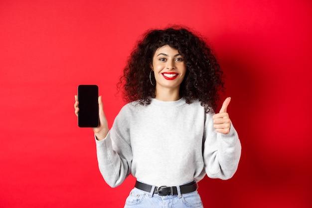 Ritratto di attraente donna sorridente con i capelli ricci, che mostra lo schermo del telefono cellulare vuoto e il pollice in su, raccomandando promo online, in piedi su sfondo rosso