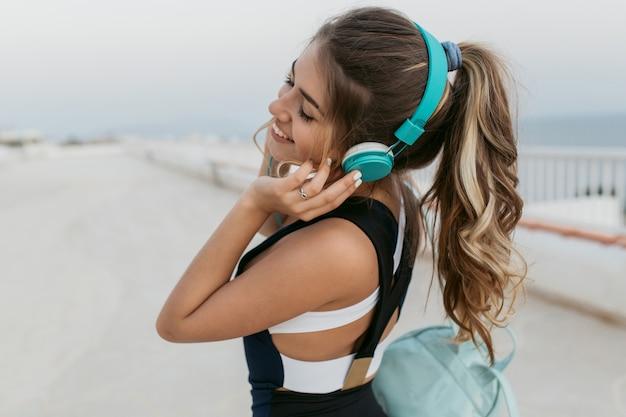 海岸沿いに早朝に歩くヘッドフォンで長い巻き毛を持つ肖像画の魅力的なスポーツウーマン。外でのトレーニング、陽気な気分、素敵な音楽、目を閉じて笑顔を楽しむ