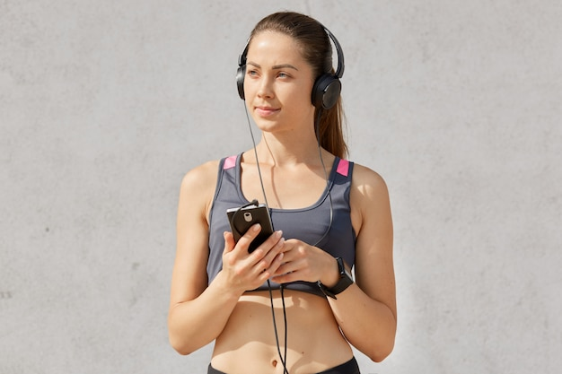 Portrait of attractive sporty woman in sportive bra listening to music with earphones and smartphone, has pony tail