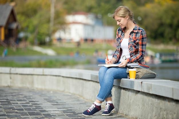 Ritratto di una ragazza attraente studente seduta a scrivere ponte