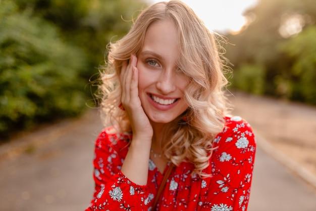 Ritratto della donna sorridente bionda alla moda attraente in vestito rosso di modo di estate della camicetta nel sorridere degli orecchini da portare di stile di boho del parco