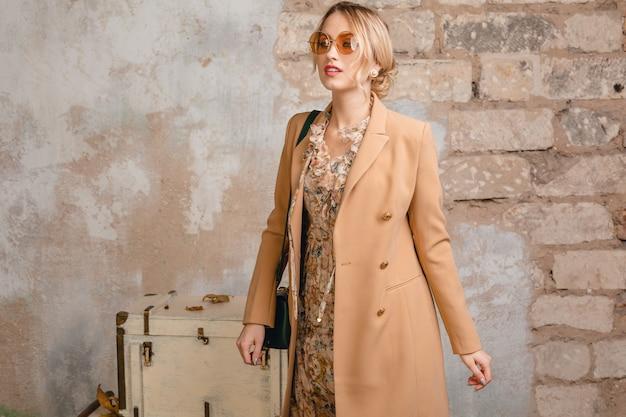Portrait of attractive stylish blonde woman in beige coat walking in street against vintage wall