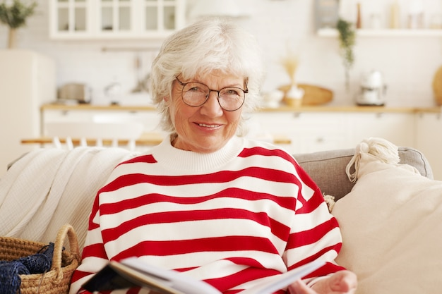 Portrait of attractive stylish european female pensioner in round eyeglasses holding book, studying art history by herself, learning on retirement, looking through pages with beaming smile