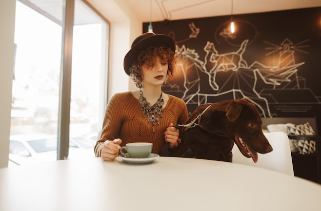 Portrait of attractive stylish girl sitting with dog in cafe at table and drinking coffee